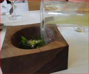 Frühlingskräuterstrauß angerichtet auf Zwiebelpüree und aufgegossen mit Zwiebelsuppe, heißer Eisenerzstein In Nussschale.